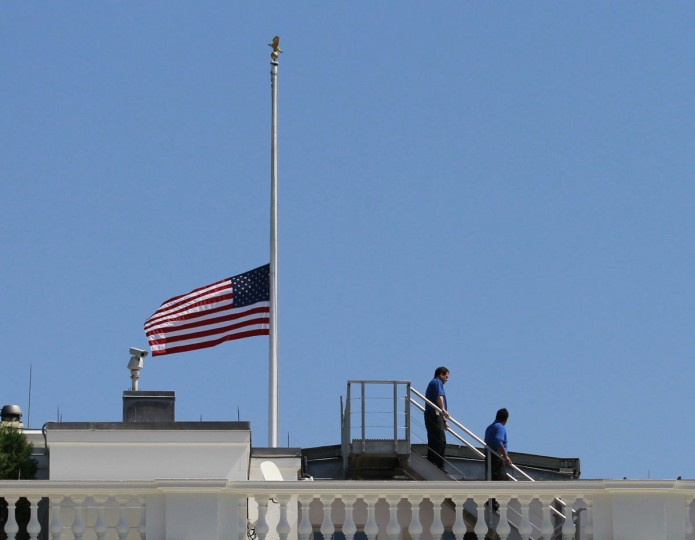 White House staff are pictured after they lowered the U.S. flag to half staff on the roof of the White House in Washington September 12, 2012, following the death of U.S. Ambassador to Libya, Chris Stevens and others in Benghazi. Stevens and three embassy staff were killed in an attack on the Benghazi consulate and a safe house refuge, stormed by Islamist gunmen blaming America for a film they said insulted the Prophet Mohammad. (Jason Reed/Reuters photo)