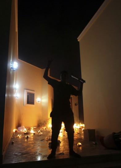 A protester reacts as the U.S. Consulate in Benghazi is seen in flames during a protest by an armed group said to have been protesting a film being produced in the United States September 11, 2012. (Esam Al-Fetori/Reuters)