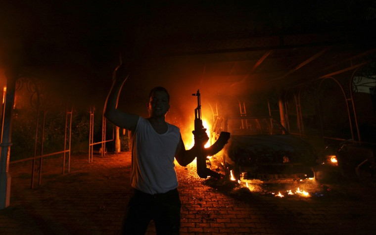 A protester reacts as the U.S. Consulate in Benghazi is seen in flames during a protest by an armed group said to have been protesting a film being produced in the United States September 11, 2012. An American staff member of the U.S. consulate in the eastern Libyan city of Benghazi has died following fierce clashes at the compound, Libyan security sources said on Wednesday. Armed gunmen attacked the compound on Tuesday evening, clashing with Libyan security forces before the latter withdrew as they came under heavy fire. (Esam Al-Fetori/Reuters)