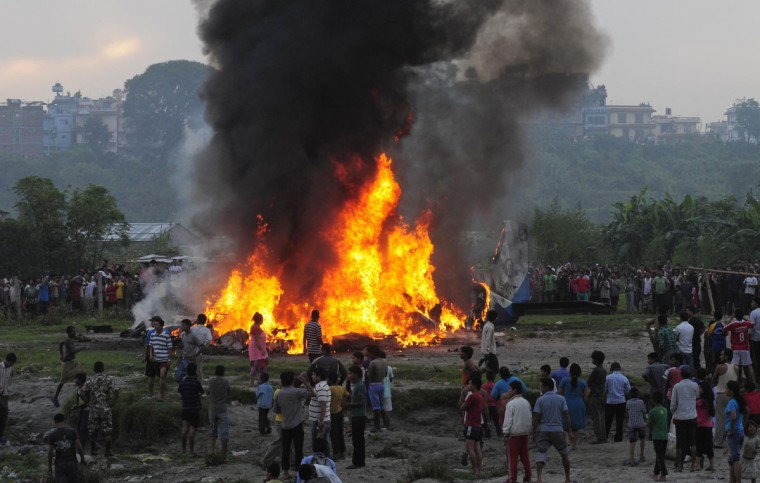 People gather near a burning Dornier aircraft after it crashed in Kathmandu. A small plane owned by private firm Sita Air crashed shortly after takeoff from the Nepali capital of Kathmandu on Friday, killing 19 people, including seven British and five Chinese passengers, an airline official said. (Stringer/Reuters)