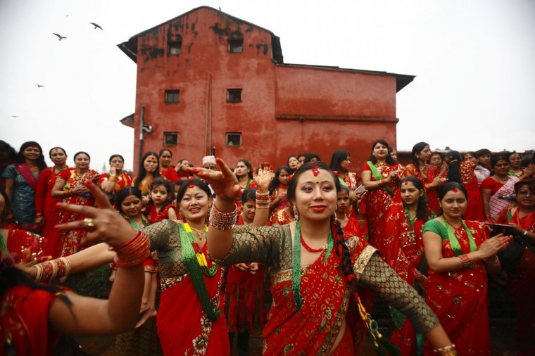 Women sing and dance at the Pashupatinath Temple during the Teej festival in Kathmandu. The three-day festival, commemorating the union of the Goddess Parvati and Lord Shiva, involves sumptuous feasts and rigid fasting. Hindu women pray for marital bliss, the well-being of their spouses and children, and the purification of their own bodies and souls during this period of religious fasting. (Navesh Chitrakar/Reuters)