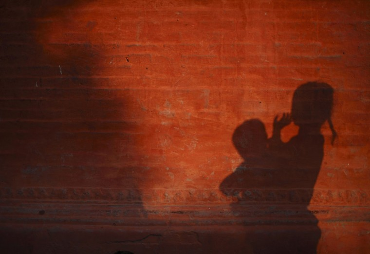 A girl carrying her younger brother casts a shadow on a wall in Lalitpur, Nepal. (Navesh Chitrakar/Reuters)