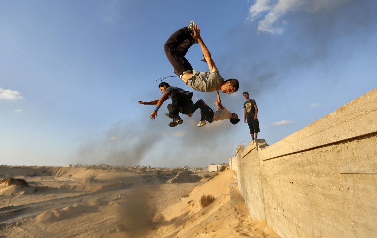 Palestinian youths practice their parkour skills in Khan Younis in the southern Gaza Strip September 12, 2012. Some youths, aged between 12 and 23 years old, in Gaza are training in parkour which was developed in France. Parkour is a physical discipline of movement focused on overcoming obstacles. Training is held in cemeteries, and in former Israeli settlements. (Mohammed Salem/Reuters photo)