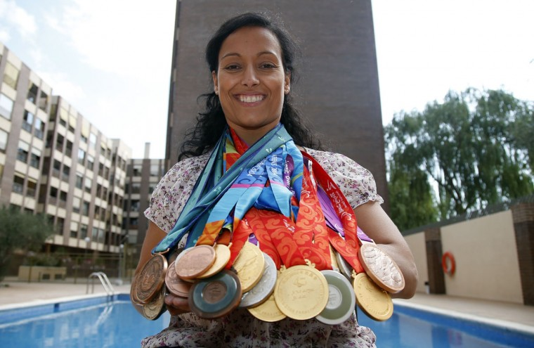 Spain's paralympic swimmer Teresa Perales poses with her 22 medals won during the four Paralympic Games she competed in, at her home in Zaragoza, September 20, 2012. A mother and a former local politician, as well as one of a handful of Paralympians with more than 20 medals, the 36-year-old Spaniard added a gold, three silvers and two bronzes in London to her combined haul of 16 at the Sydney, Athens and Beijing Games, putting her level with the athlete many consider the greatest Olympian, American swimmer Michael Phelps. (Sergio Perez/Reuters)