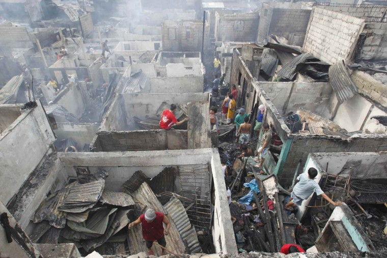 Residents try to salvage their belongings after a fire that razed some 200 houses during dawn, in Quezon City, Metro Manila. One person died and left at least 800 families homeless after the fire, local media reported. (Cheryl Ravelo/Reuters photo)