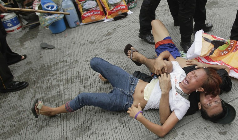 An illegal settler cries as she lies on the ground with her husband after they were arrested by members of the SWAT police team during a demolition in Manila's Makati financial district September 24, 2012. (Erik De Castro/Reuters)