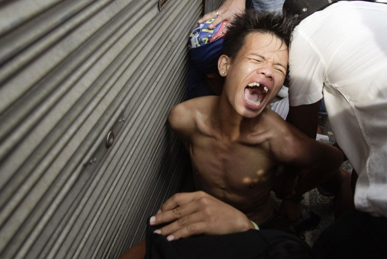 An illegal settler grimaces after being arrested from supposedly throwing rocks at the police during a demolition in Manila's Makati financial district September 24, 2012. Dozens of slum residents of an abandoned government compound clashed with the police on Monday in an attempt to block a demolition order issued by the local government. (Erik De Castro/Reuters)
