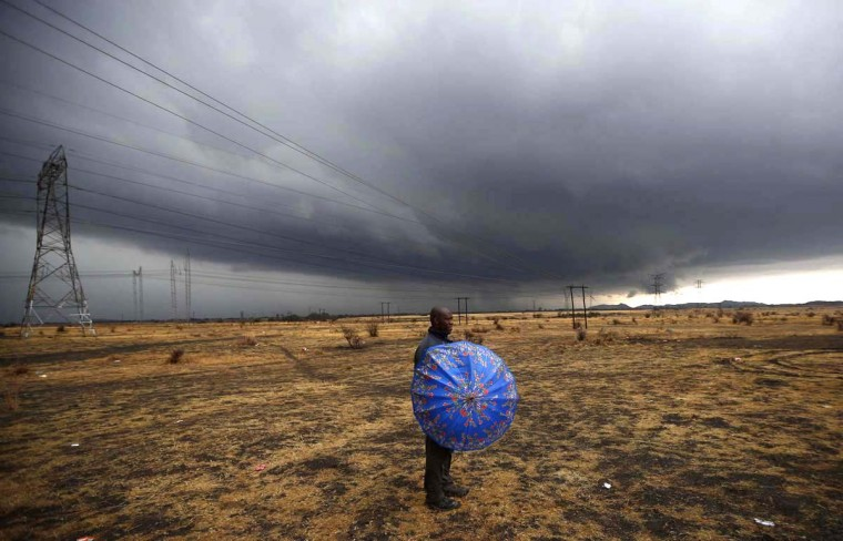 "A striking mineworker holds an umbrella as he awaits a ""report back"" meeting near Lonmin's Marikana mine in South Africa's North West Province. South Africa's militant AMCU union refused to sign a ""peace deal"" with platinum company Lonmin on Thursday, undermining government-backed efforts to open pay talks and end a four-week strike scarred by deadly violence. (Mike Hutchings/Reuters photo)"