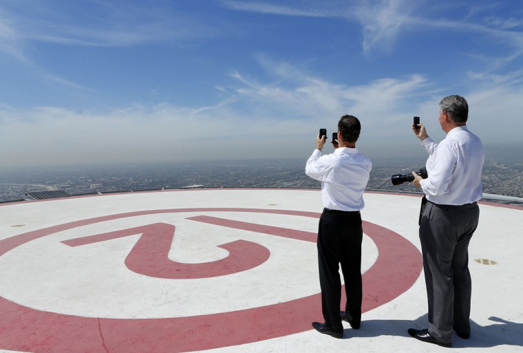 Businessmen use mobile phones to record the arrival of the Space Shuttle Endeavour on top of a building in downtown Los Angeles September 21, 2012. Endeavour will be moved to its permanent home at the California Science Center in October. (Mike Blake/Reuters)