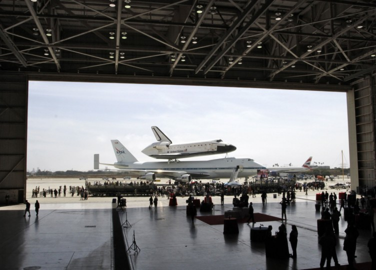 People watch the landing ceremony outside a hangar for the arrival of Space Shuttle Endeavour on the back of a 747 at Los Angeles International Airport September 21, 2012. Endeavour will be moved to its permanent home at the California Science Center mid-October. (Jonathan Alcorn/Reuters)