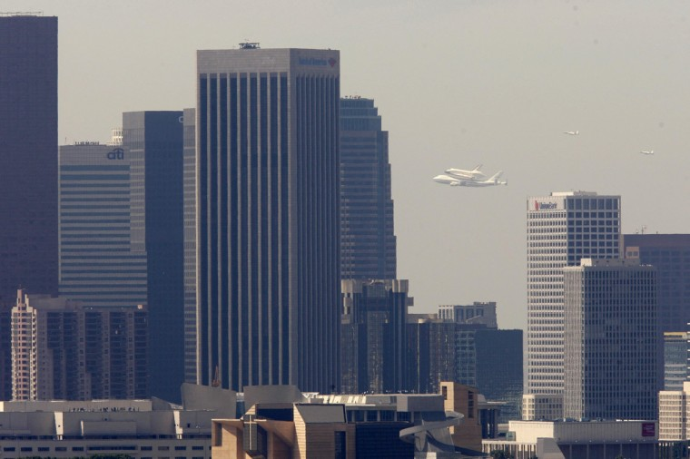 The Space Shuttle Endeavour passes downtown as it arrives on the back of a 747 en route to Los Angeles International Airport September 21, 2012. (David McNew/Reuters)