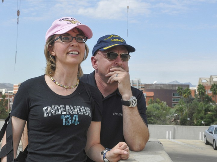 Former U.S. Congresswoman Gabrielle Giffords and her husband Mark Kelly, the retired astronaut who commanded space shuttle Endeavour's final flight on his last mission in late May 2011, watch Endeavour and its carrier jet making a flyover over Tucson, Arizona, September 20, 2012. Giffords, still recuperating from a gunshot wound to the head suffered in an attempt on her life last year, watched the flyover from the roof of a Tucson parking garage with her husband and mother, according to former aide C.J. Karamargin, who joined them. (Handout/Reuters)