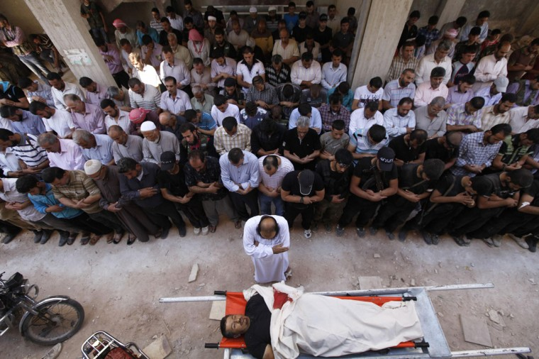 Civilians and Islamist fighters pray over the body of Tareq Naser, an Islamist fighter who died during clashes on Sunday, during his funeral near the village of Fafeen in Aleppo's countryside September 17, 2012. (Zain Karam/Reuters)