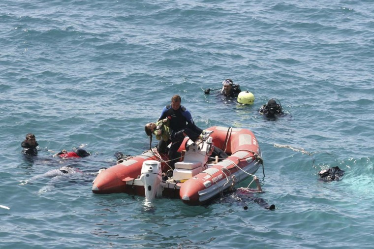 A diver from the Turkish sea police (C) carries a girl in a rescue boat as other divers look for victims in the Aegean sea off Menderes, western Turkey. At least 39 people were dead and many more were missing after a boat carrying illegal migrants sank off Turkey's western Aegean coast on Thursday morning, a district governor said. Tahsin Kurtbeyoglu, the governor of Menderes, a coastal district in Izmir province, told state television TRT he expected the death toll to rise. (Safak Yel/Ihlas News Agency thru Reuters)
