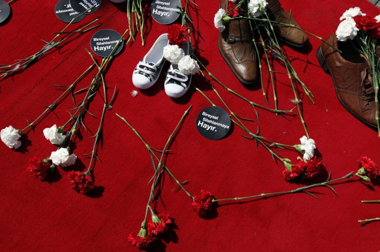 "Shoes, carnations and signs that read ""No to individual armament"" are seen laid on a red carpet by relatives of gunfire victims and other participants during an anti-gun rally on Individual Disarmament Day in central Istanbul. A group of people who lost relatives by gunfire gathered in central Istanbul to commemorate their loss and to support the individual disarmament campaign organised by the Umut Foundation. (Murad Sezer/Reuters)"