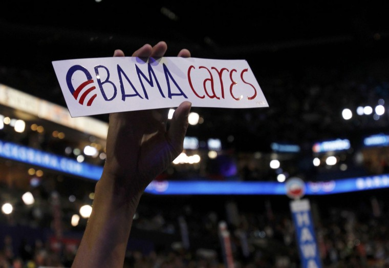 """A delegate holds an """"Obama cares"""" bumper sticker during the final session of the Democratic National Convention in Charlotte, North Carolina September 6, 2012. (Jessica Rinaldi/Reuters)"""