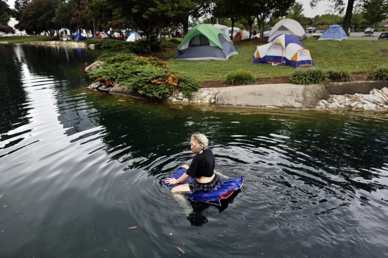 A female protester rides a float in a pond at Marshall Park during the second day Democratic National Convention in Charlotte, North Carolina September 5, 2012. The protesters gathered as the park to use it as an encampment. (John Adkisson/Reuters)
