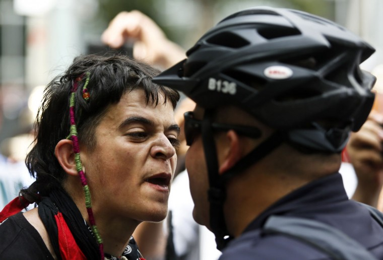 A demonstrator (Left) confronts a police officer while marching during the final day of the Democratic National Convention in Charlotte, North Carolina September 6, 2012. (John Adkisson/Reuters)