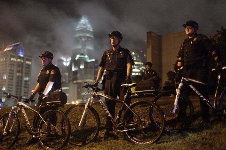 Police officers stand guard as demonstrators march during the first day of the Democratic National Convention in Charlotte, North Carolina, September 4, 2012. The demonstration was held to protest against capitalism. (John Adkisson/Reuters)