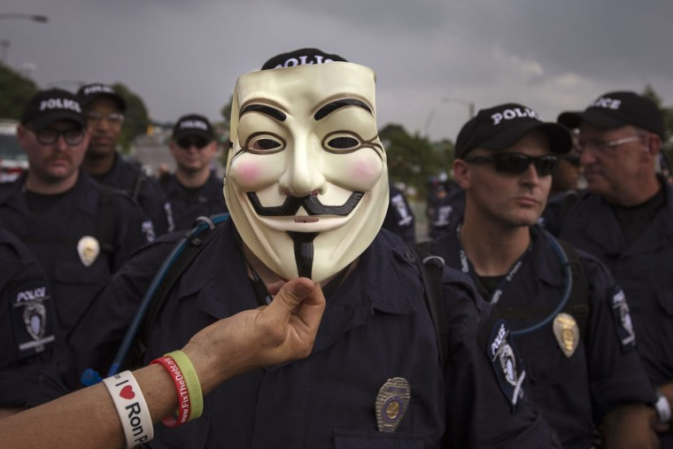 A demonstrator holds a Guy Fawkes mask in front of a line of police officers blocking a protest march near the site of the Democratic National Convention in Charlotte, North Carolina on September 4, 2012. (Adrees Latif/Reuters)