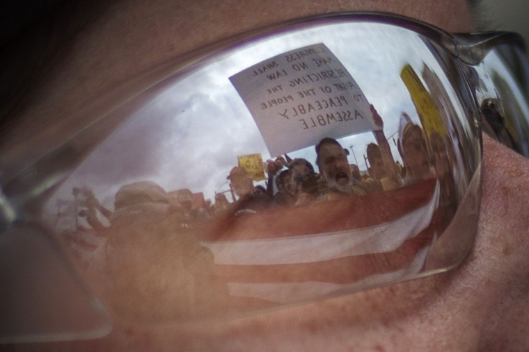 Demonstrators holding the U.S. Flag and a placard are reflected in the glasses of a police officer blocking protesters marching near the site of the Democratic National Convention in Charlotte, North Carolina on September 4, 2012. (Adrees Latif/Reuters)