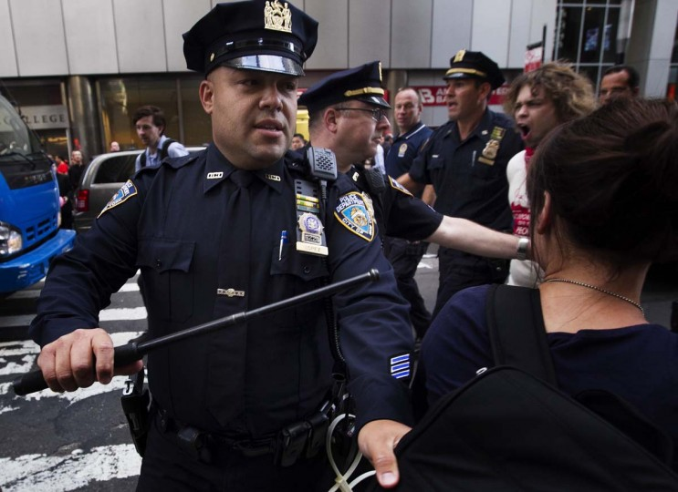 An Occupy Wall Street activist is pushed off the street by a New York Police Department officer while demonstrating in the financial district during the one-year anniversary of the movement in New York. (REUTERS/Lucas Jackson)
