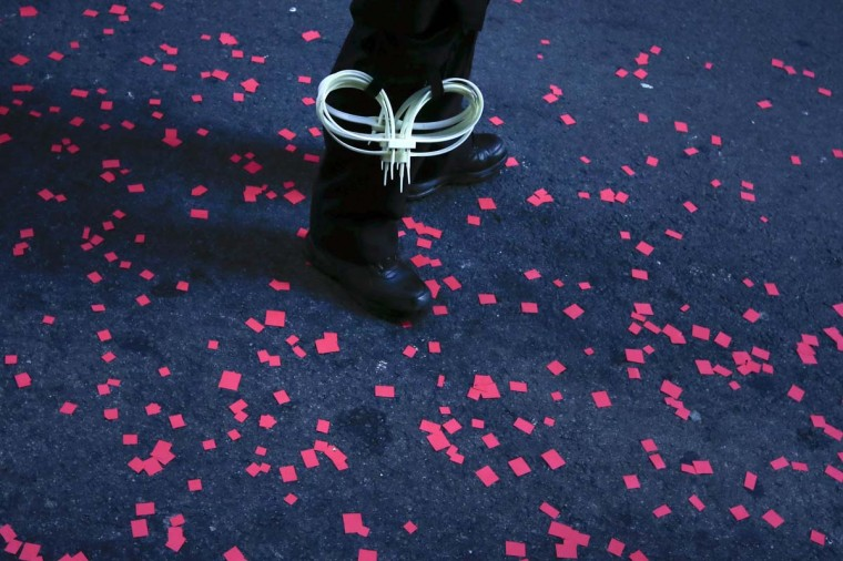 A policeman stands guard near Occupy Wall Street activists who sprayed confetti while matching past the financial district in Lower Manhattan on the one-year anniversary of the movement in New York. (REUTERS/Adrees Latif)