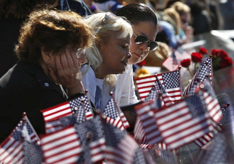 Rema Weiser, Virginia Pacheco and Dinah Pacheco (from L) pause at the edge of the North Pool of the 9/11 Memorial during ceremonies marking the 11th anniversary of the 9/11 attacks on the World Trade Center in New York, September 11, 2012. (Mike Segar/Reuters)