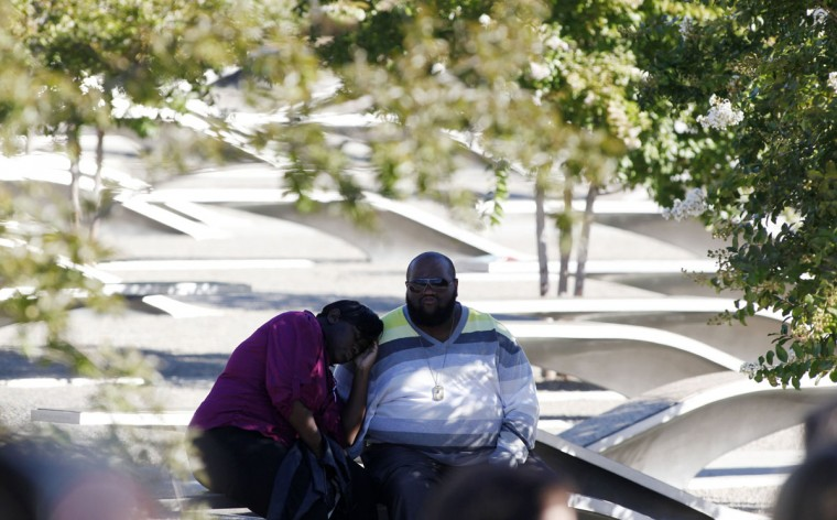 An unidentified couple sit on a bench during a memorial service on the 11th anniversary of the attacks of September 11, 2001 to honor the 184 people who lost their lives when American Airlines flt. 77 crashed into the Pentagon, outside Washington, September 11, 2012. (Larry Downing/Reuters)