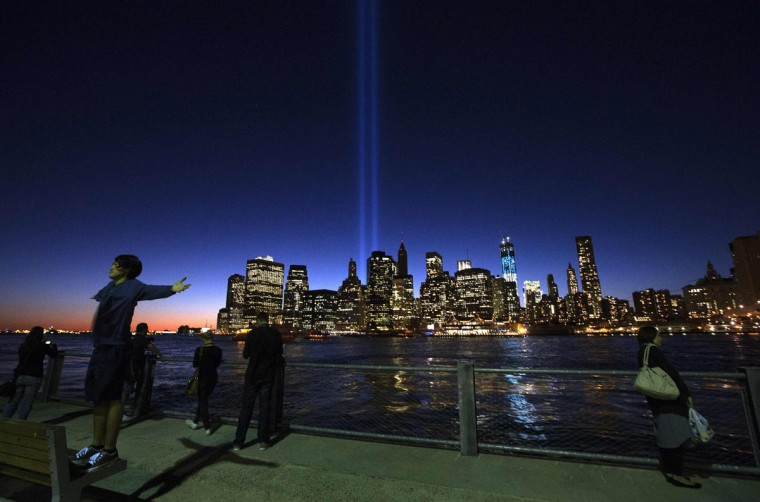 The Tribute in Light illuminates the sky over New York's lower Manhattan skyline a day ahead of the 11th anniversary of the 9/11 attacks as Natsuki, of Yokohama, Japan, raises his arms for a portrait in New York September 10, 2012. The Tribute in Light is an art installation near the site of the World Trade Center in remembrance of the September 11 attacks. (Adrees Latif/Reuters)