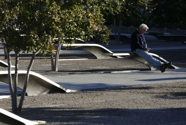 An unidentified man sits alone on a bench before a memorial service on the 11th anniversary of the attacks of September 11, 2001 to honor the 184 people who lost their lives when American Airlines flt. 77 crashed into the Pentagon outside Washington, September 11, 2012. (Larry Downing/Reuters)