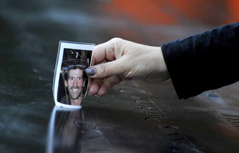 Christine Gonda places a picture of firefighter George Kane at the engraving of his name at the South Pool during ceremonies marking the 11th anniversary of the 9/11 attacks on the World Trade Center, in New York, September 11, 2012. (Justin Lane/Reuters)