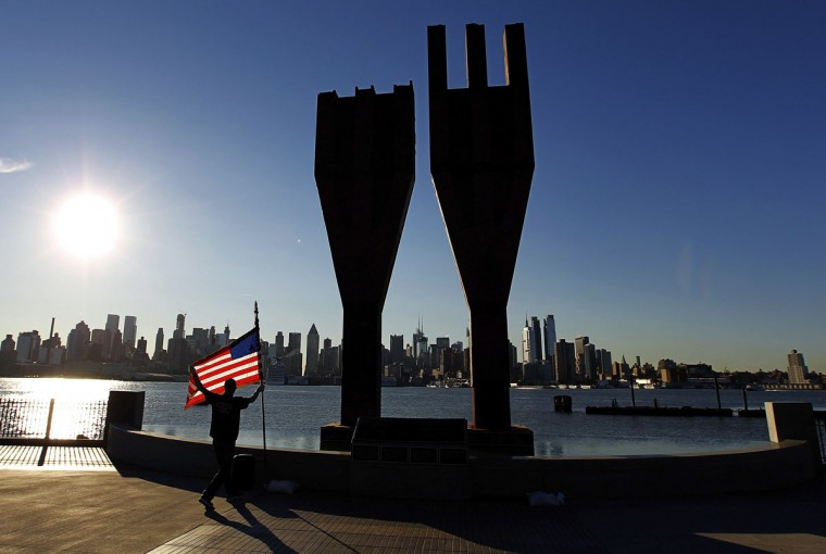 Jeremy Hamilton places a U.S. flag next to a memorial bearing two pieces of steel from the World Trade Center in Weehawken, New Jersey, across from the skyline of New York, September 11, 2012. Thousands will gather in New York, Washington and Pennsylvania to mark the 11th anniversary of the September 11 attacks. (Gary Hershorn/Reuters)
