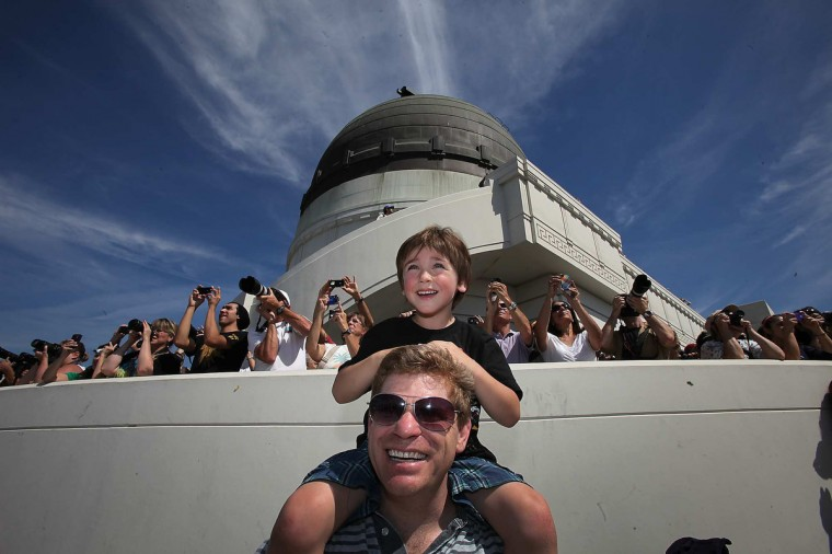 Shuttle fan Jacob Kreinbring, 5, sits on dad Dan's shoulders as they watch the space shuttle Endeavour fly over Griffith Park Observatory September 21 2012 in Los Angeles. The shuttle is scheduled to land at LAX Friday afternoon. (Brian van der Brug/Los Angeles Times)