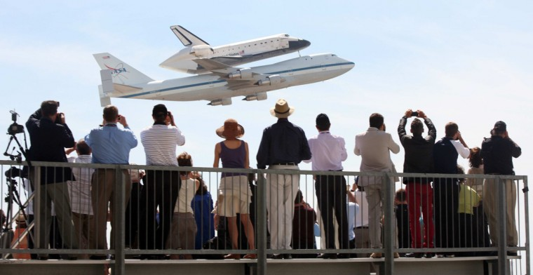 The space shuttle Endeavour makes a low flyover, atop a modified Boeing 747, in front of spectators at the welcoming ceremony at Los Angeles International Airport. (Bryan Chan / Los Angeles Times)