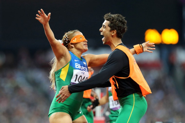 Terezina Guilhermina of Brazil with her guide Guilherme Soares de Santana celebrate winning a Gold Medal in the Women's 200m T11 Final during the London 2012 Paralympic Games at Olympic Stadium on September 2, 2012. (Paul Cunningham/US Presswire)