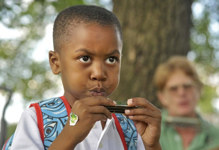"""Zaire Hursey, 5, of Baltimore, tries out a harmonica given to him at the Druid Hill Farmers Market by Will Blair of Blair Live Acoustics."""" Zaire explained, """"You have to blow into it."""" (Amy Davis /Baltimore Sun)"""