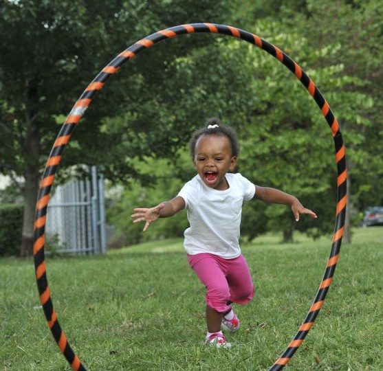 London Carry, 2, has fun with a hula hoop at the Druid Hill Farmers Market, where she came with her grandparents. (Amy Davis/Baltimore Sun)