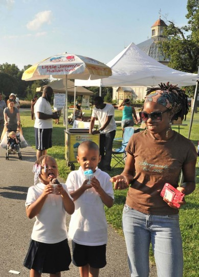 Makiyah, left, and Shawn Hardison, ages 4 and 6 respectively, enjoy Italian Ices while their mother Deneise Wilson watches on. They are at the Druid Hill Farmers Market. (Amy Davis/Baltimore Sun)