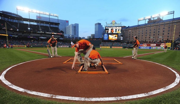 Grounds crew members are marking the batter's boxes and the catcher's box around the frame, which will then be chalked, before the start of the game between the Baltimore Orioles and the Toronto Blue Jays. (Gene Sweeney Jr. /Baltimore Sun)