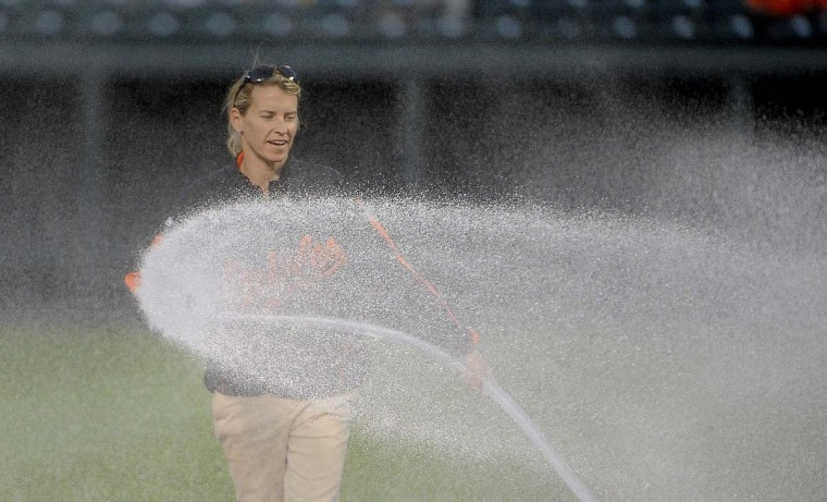 Head groundskeeper, Nicole Sherry, sprays the infield dirt to settle it before the start of the game between the Orioles and the Toronto Blue Jays. The hose delievers water at 150 psi and takes a crew of five to manage it while Sherry sprays the infield. (Gene Sweeney Jr. /Baltimore Sun)