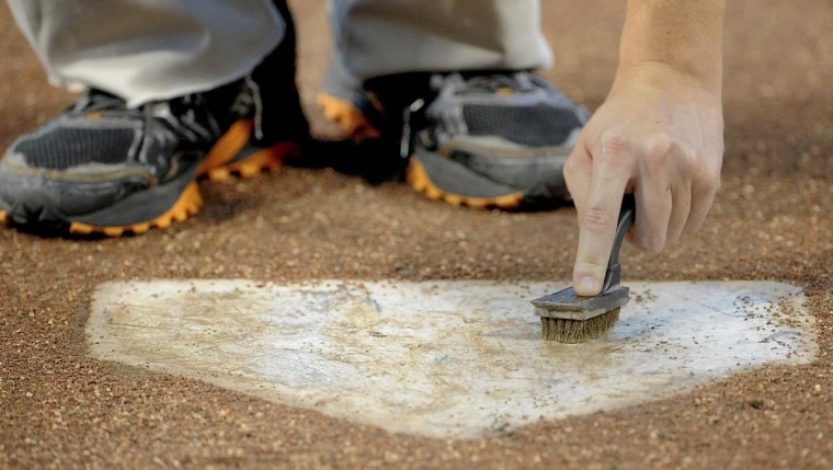 Thomas Kirsch cleans home plate with tire cleaner and a brush before the start of the Orioles game against Toronto. (Gene Sweeney Jr. /Baltimore Sun)