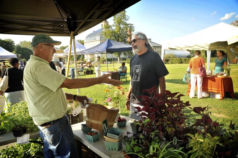 Farmer John Polhemus, left, of Crossroads Farm in Baltimore, chats with Don Palmer, who was seeking parsley at the Druid Hill Farmers Market for a recipe using crowder peas, shrimp and okra.( Amy Davis/Baltimore Sun)