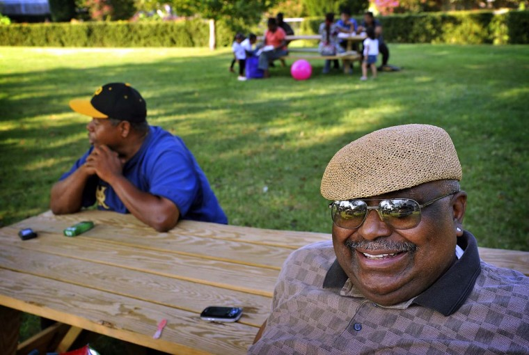 """William Johnson, right, of Baltimore relaxes at a picnic table at the Druid Hill Farmers Market. He enjoys the friendly atmosphere where he is able to strike up a conversation with strangers such as Carey Cheek, seated at left. Cheek agreed that the atmosphere is """"very serene and the food is good."""" (Amy Davis/Baltimore Sun)"""
