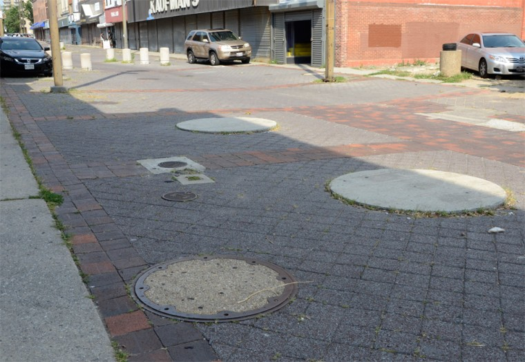 August 9, 2012 - Today, concrete slabs mark where planters once stood. Utility hole covers often indicate where light posts were installed. (Olivia Hubert-Allen/Baltimore Sun photo)