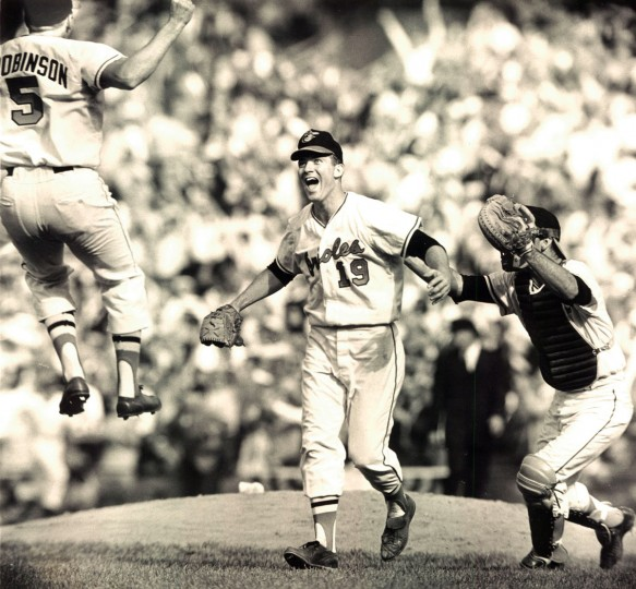 "Brooks Robinson (5) seems to fly from third base to celebrate the Orioles 1966' World Series sweep with pitcher Dave McNally (19) as catcher Andy Etchebarren rushes in. People still ask Robinson, ""How did you jump so high?"" (Paul Hutchins/Baltimore Sun)"