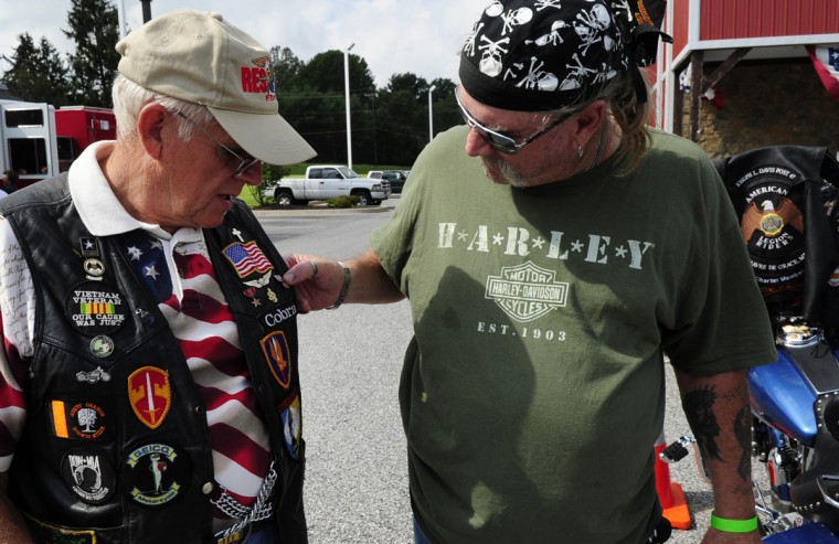 "Friends Dick ""Cobra"" Smalley, left, and Bruce ""Bam Bam"" Maxwell, talk about the Purple Heart pin on Smalley's vest while wait for Saturday's Patriot Day Ride to begin at Chesapeake Harley-Davidson. (Matt Button/Aegis Staff)"