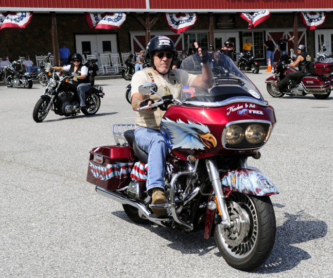 """Veteran B.J. Fischbach gives the """"thumbs up"""" as he rolls out on his custom painted 2009 Harley-Davidson Road Glide tribute bike during Saturday's Patriot Day Ride. (Matt Button/Aegis Staff)"""
