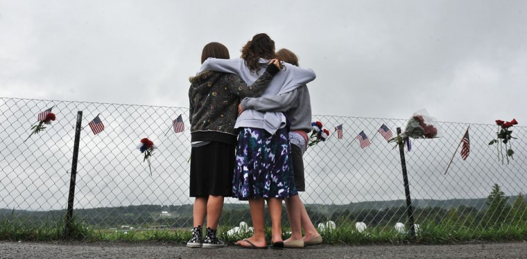 Courtney Peller (R), 14, Taylor Duffy (C) and Caitlin Rakowski, both 15, embrace as they look at the field in Shanksville, Pennsylvania, on September 9, 2011, where United flight 93 crashed on September 11, 2001. (Nicholas Kamm/AFP/Getty Images)