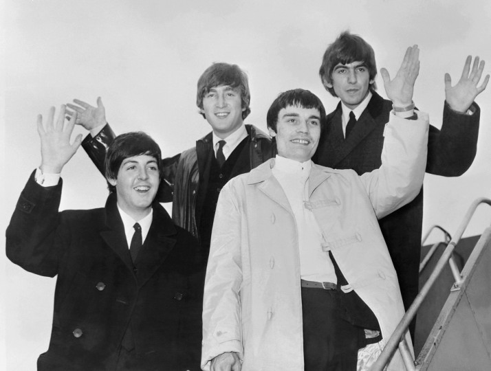 The Beatles, (from L to R) Paul McCartney, John Lennon, Jimmy Nicol and George Harrison, salute as they leave London, in June 1964, as they go on tour in Scandinavia. Ringo Starr, ill, was temporarily replaced for the Denmark and Holland concert dates by drummer Jimmy Nicol. (Getty Images)